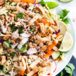Crunchy Thai Chicken Salad in white bowl on gray towel with limes