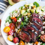 Steak Blue Cheese Avocado Salad in white bowl with blue striped towel