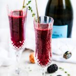 Blackberry bellini in champagne flutes with thyme and a bottle of prosecco