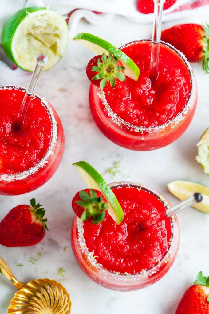 Frozen Strawberry Margaritas in glasses with lime and strawberry garnish