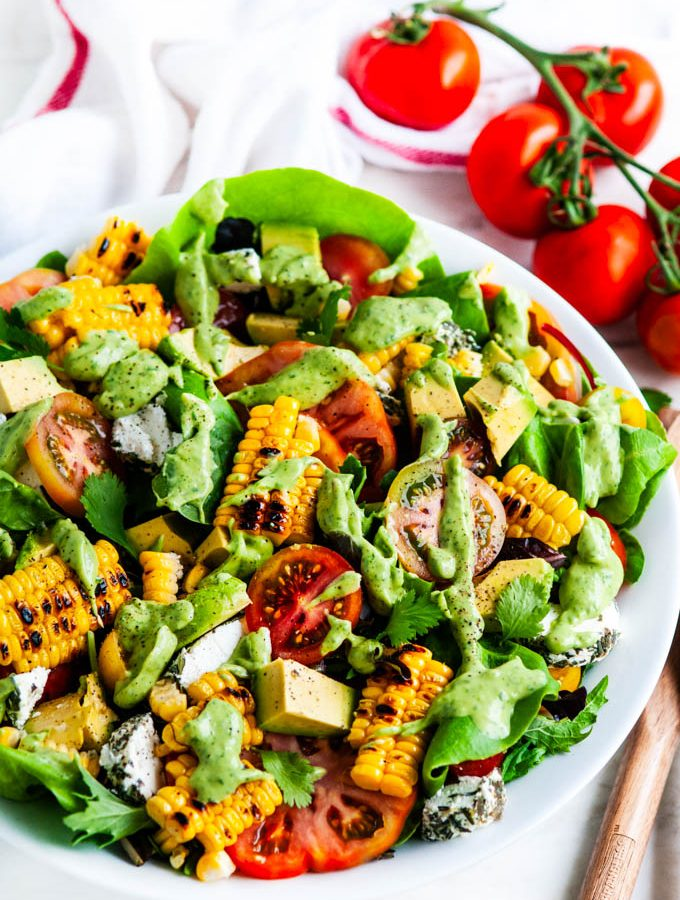 Grilled Corn Tomato Salad with Cilantro Avocado Dressing in a white bowl with serving tongs
