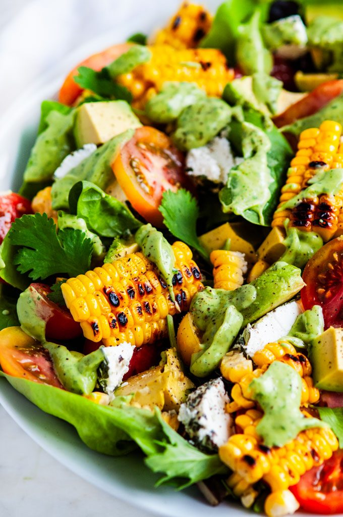 Grilled Corn Tomato Salad with Cilantro Avocado Dressing in a white bowl close up