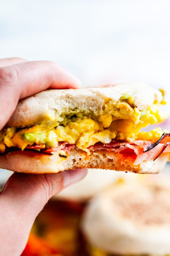 Bite of Make Ahead Freezer Breakfast Sandwiches with eggs, ham, and avocado in hand