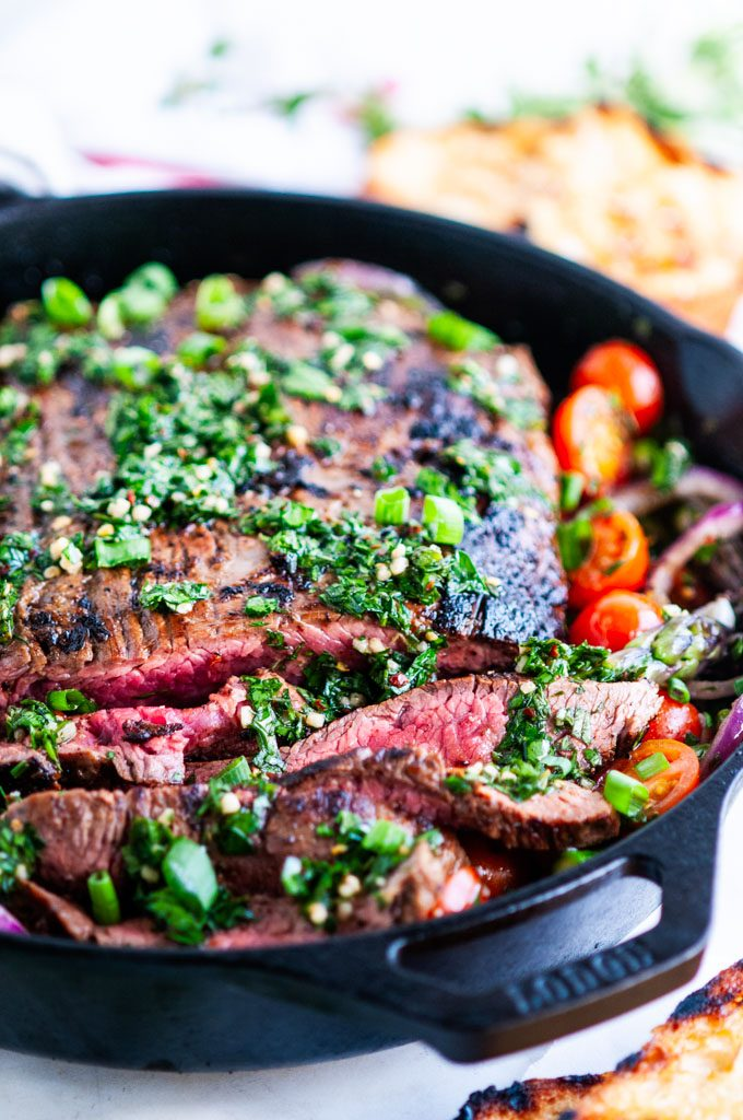 Skillet flank steak in cast iron skillet with tomatoes, asparagus, and grilled bread close up