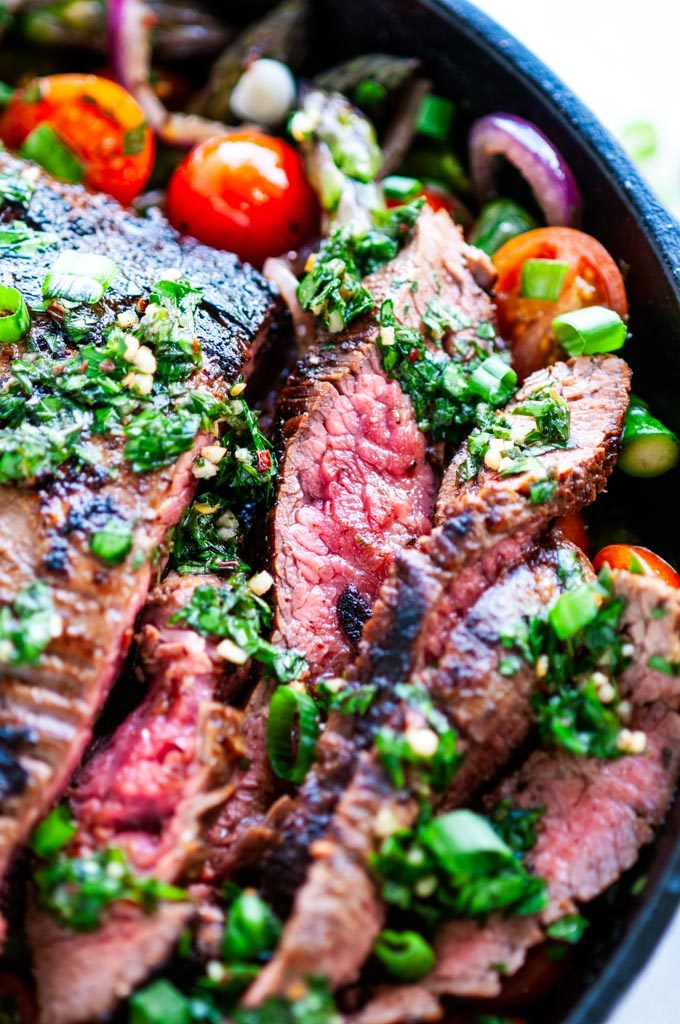 Skillet flank steak in cast iron skillet with tomatoes and asparagus close up