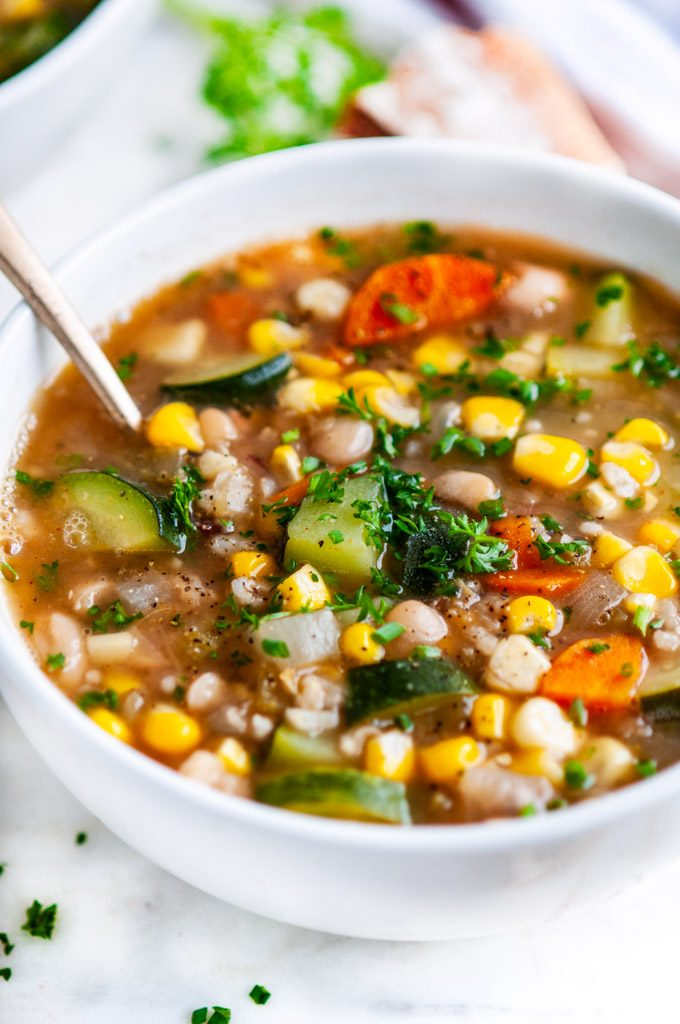 Summer Corn Zucchini White Bean Soup close up in a white bowl with gold spoon