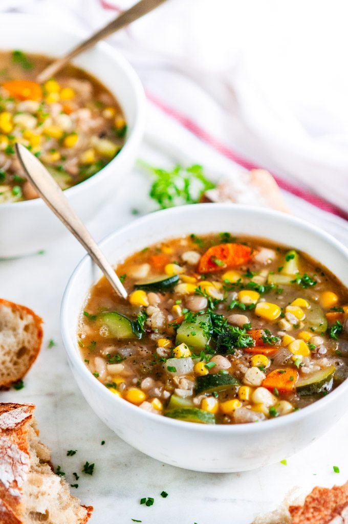 Summer Corn Zucchini White Bean Soup in a white bowl with gold spoon