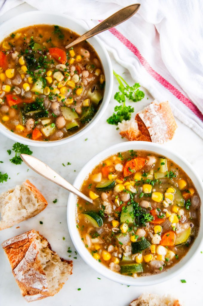 Summer Corn Zucchini White Bean Soup in white bowls with gold spoon and bread