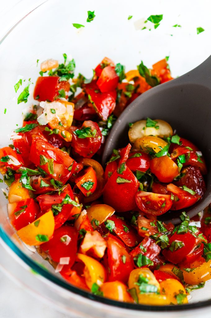 Tomato Basil Bruschetta topping in a clear bowl with a gray spoon