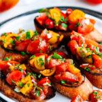 Tomato Basil Bruschetta on a white plate and gray platter