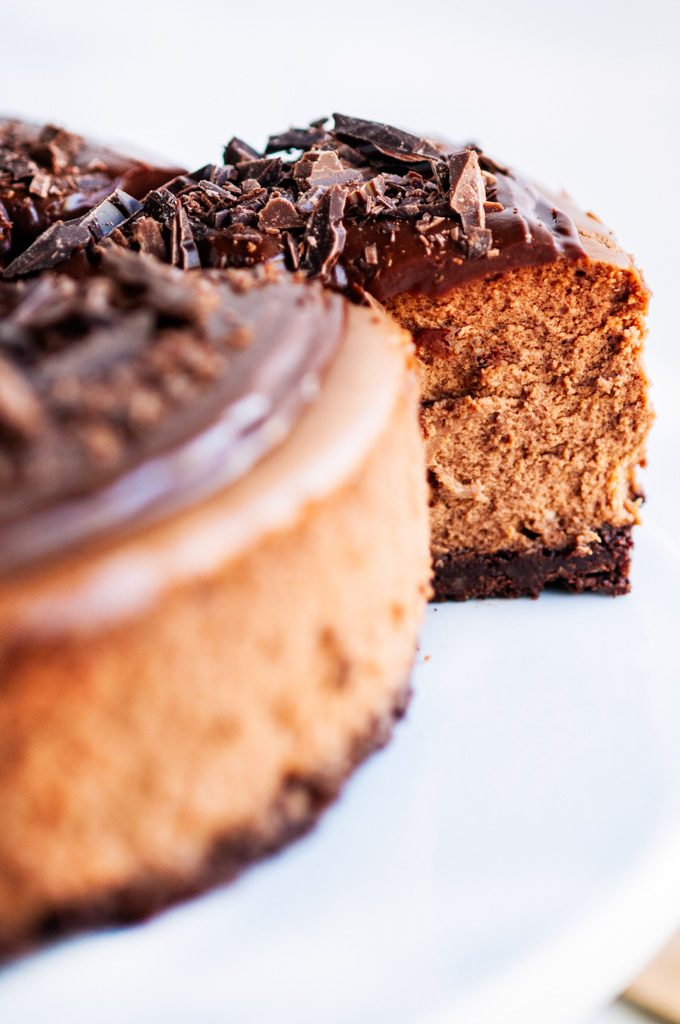 Triple Chocolate Cheesecake slice removed with chocolate ganache and chocolate shavings