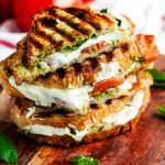 Caprese panini with avocado basil pesto stack on wooden board with tomato