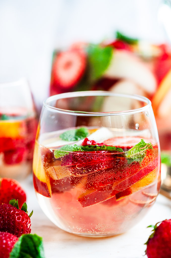 Peach Strawberry White Wine Sangria in wine glasses with gold spoons and fruit