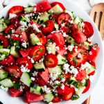 Watermelon Strawberry Cucumber Salad with wooden serving spoon and towel