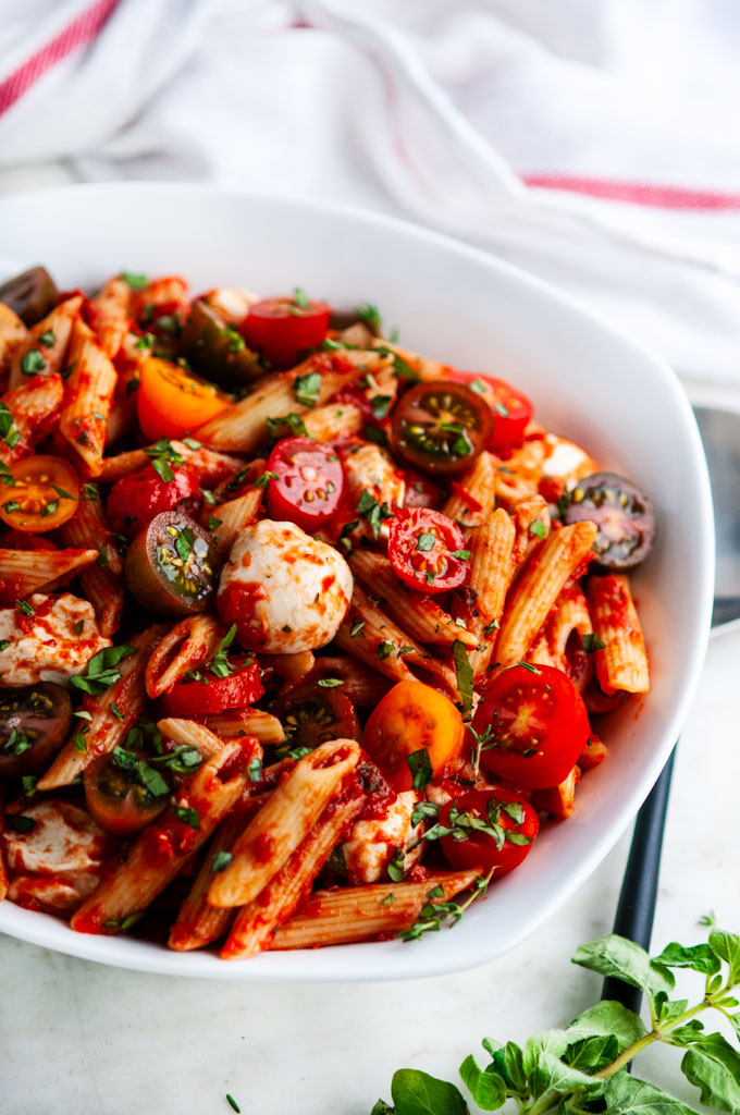 Caprese Pasta with Marinara Sauce in white bowl with red striped towel