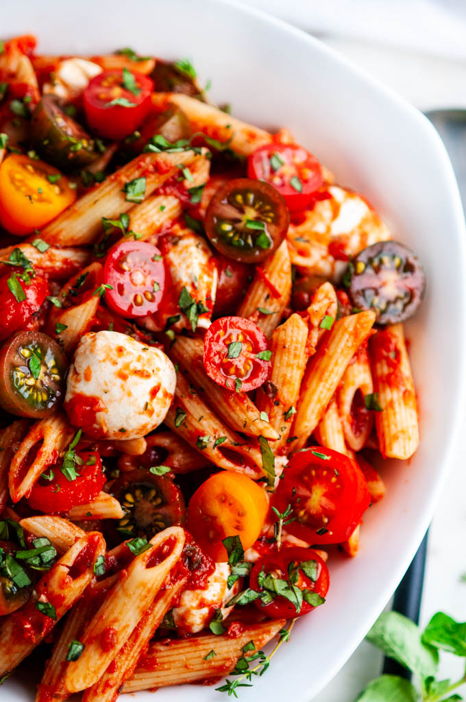 Caprese Pasta with Marinara Sauce in white bowl with herbs close up