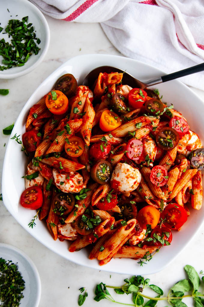 Caprese Pasta with Marinara Sauce in white bowl with herbs and red striped towel