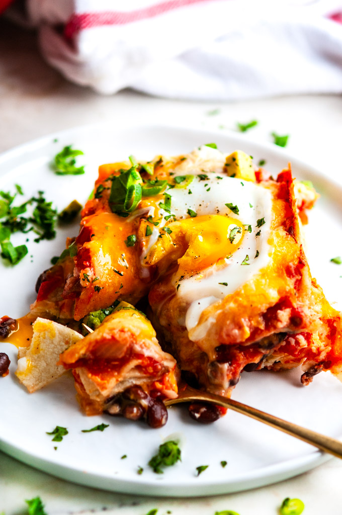 Cheesy Baked Huevos Rancheros Casserole slice on white plate with gold fork