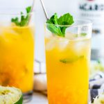 Fresh Mint Mango Mojito glasses with limes and gold spoons