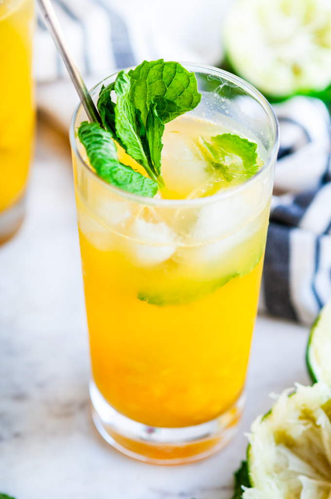 Fresh Mint Mango Mojito glass with limes and gold spoon