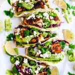 Blackened Cod Fish Tacos with Cilantro Avocado Sauce and limes on parchment paper
