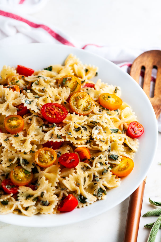 Creamy Goat Cheese Spinach Pasta with white bowl and wooden spoon