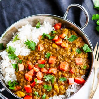 One Pot Lentil Dal in silver bowl with gold forks and gray towel