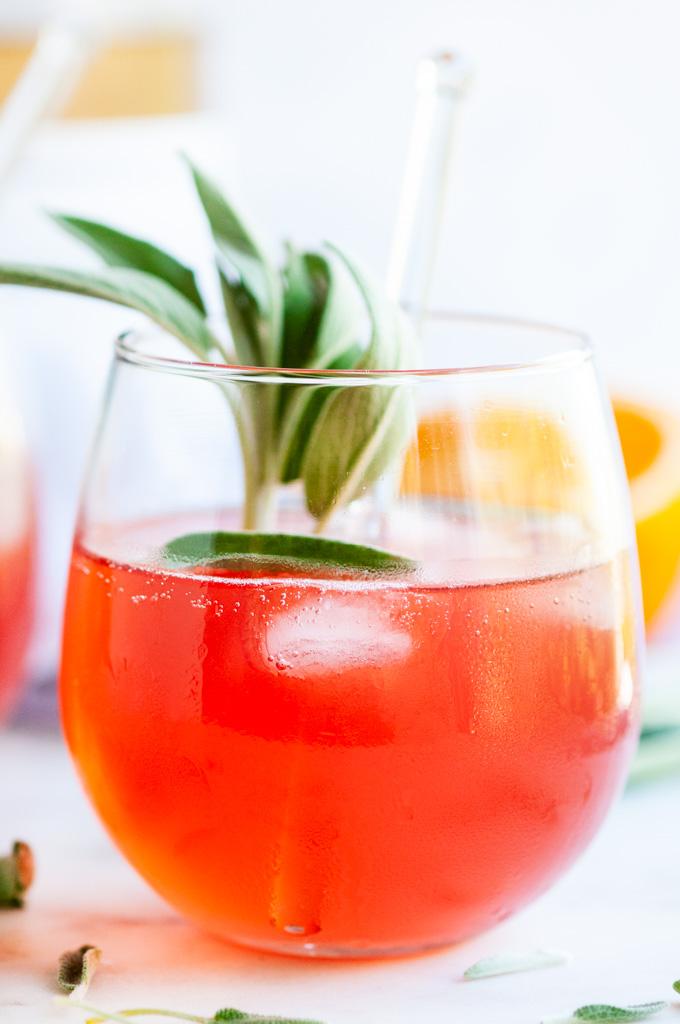 Sage Ginger Blood Orange Fizz Cocktail stemless glass with stirrer, fresh sage and halved oranges