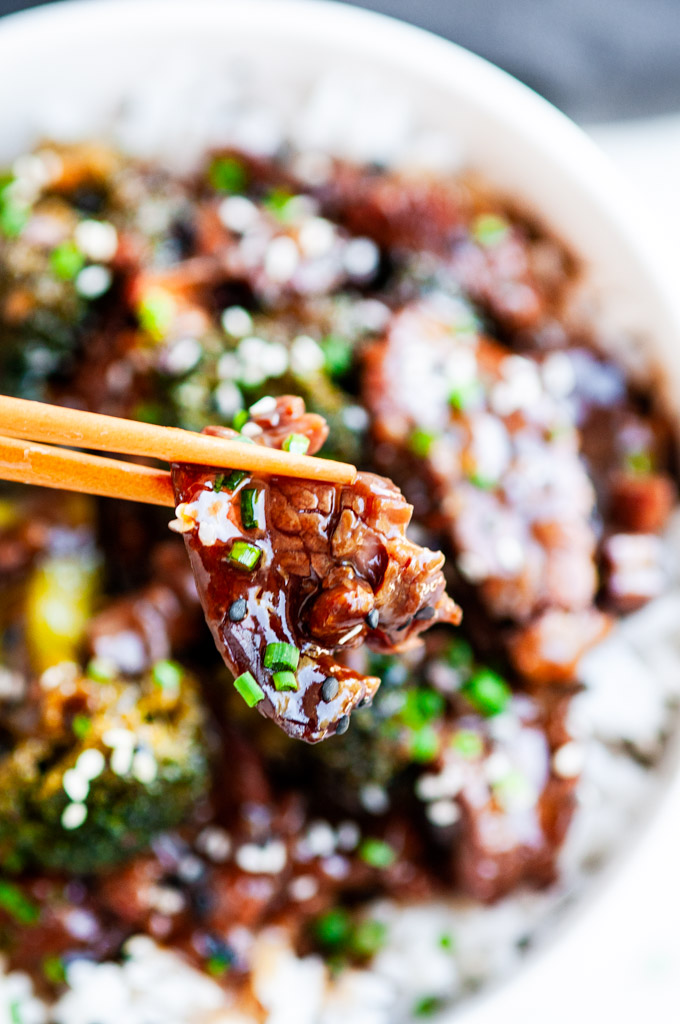 Slow Cooker Beef and Broccoli bite chopsticks in front of bowl