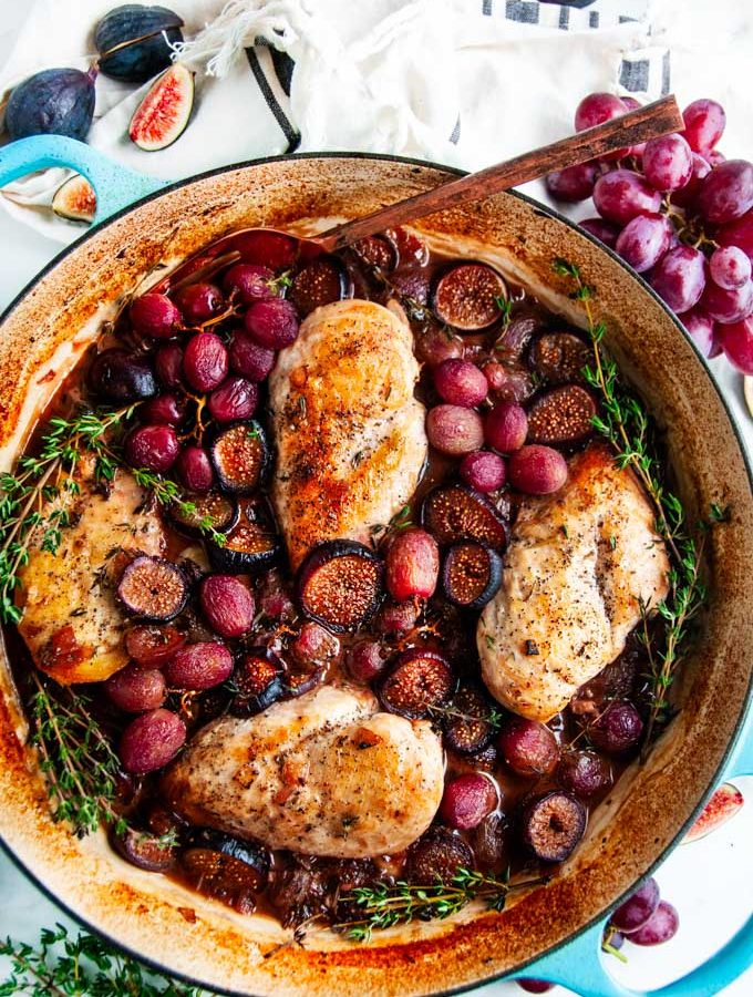 Braised Chicken with Figs and Grapes in blue le creuset braiser with fresh thyme