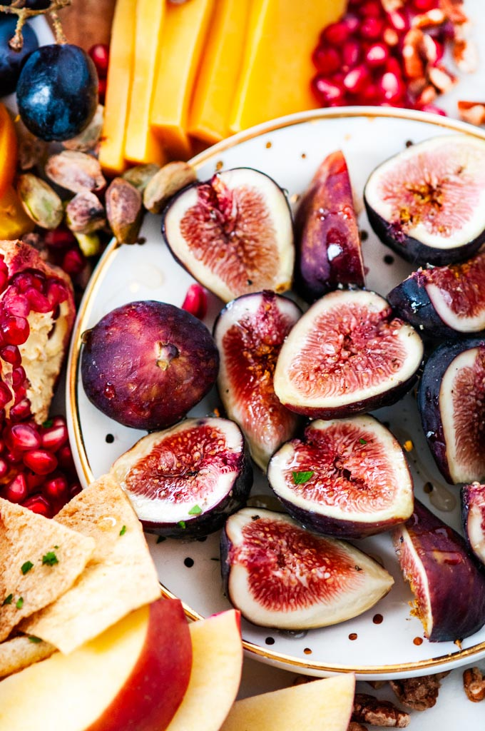 Greek Autumn Cheese Board honey drizzled figs on a white gold polka dot plate with pita chips, pomegranate seeds and pisatchios
