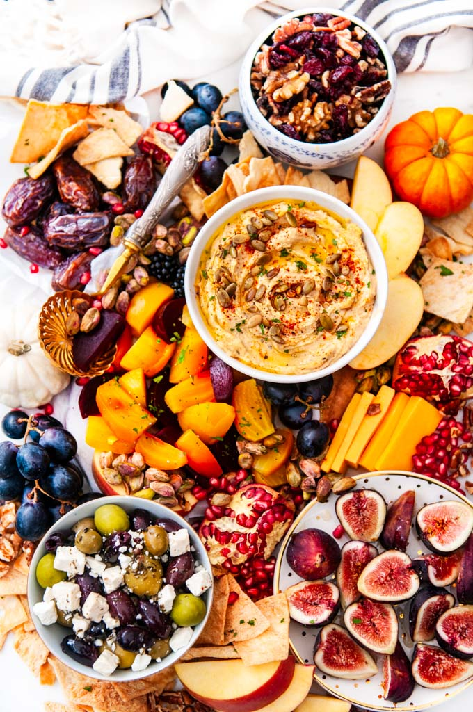Greek Autumn Cheese Board on white marble with hummus, gold and red beets, honey drizzled figs and dates, olives and feta cheese, grapes, apples, cheddar cheese, pomegranate seeds, pistachios, nuts, cranberries and pita chips
