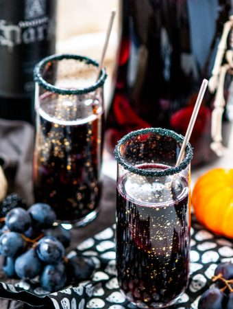 Halloween Witches Brew Black Sangria in gold sparkle star glasses with skull paper, pumpkins and pitcher