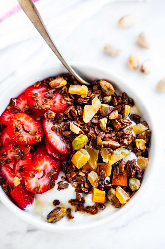 Pistachio Mango Granola white bowl strawberries and honey with a gold spoon