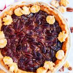 Deep dish bourbon pecan pie on marble with white towel red stripe