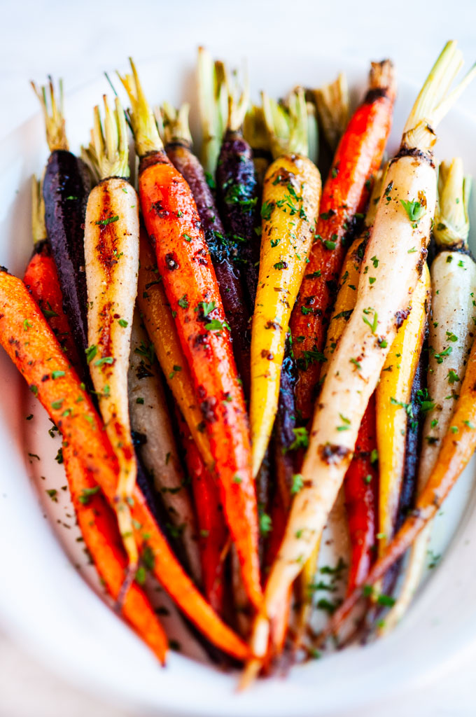 Honey garlic roasted carrots white serving platter on white marble