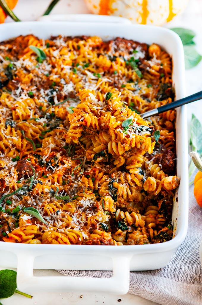 Pumpkin Sausage Spinach Pasta Bake in white pan with black metal spoon