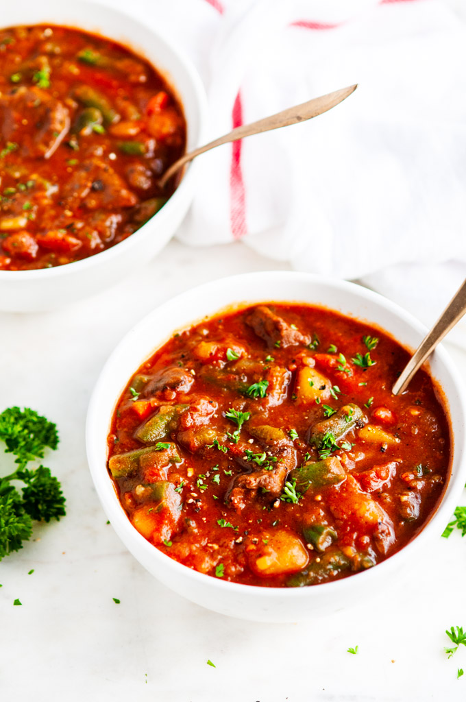 Hearty beef stew in white soup bowl with gold spoon