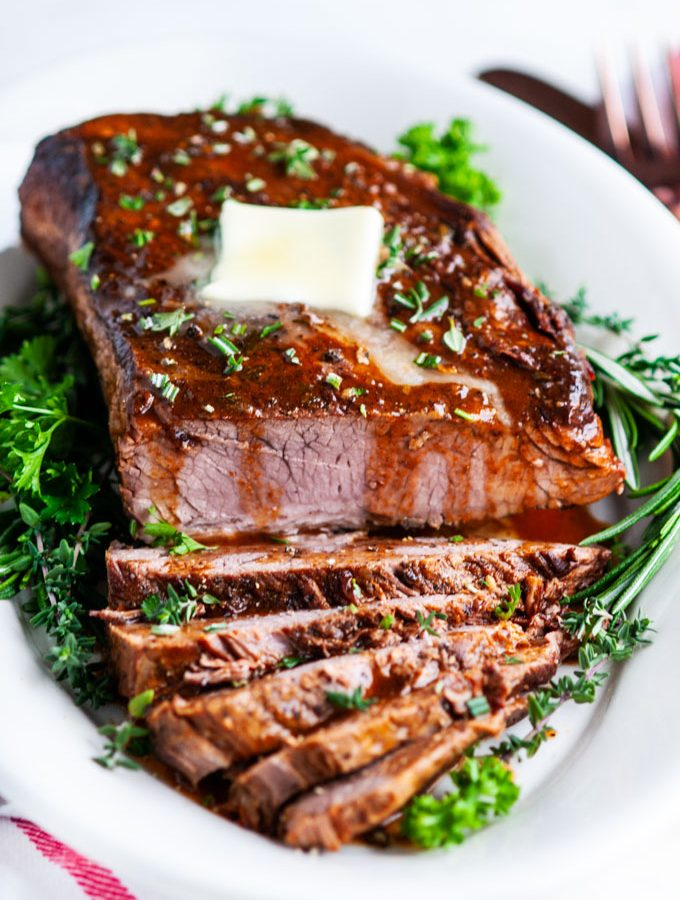 beef brisket sliced with butter and herbs on white platter