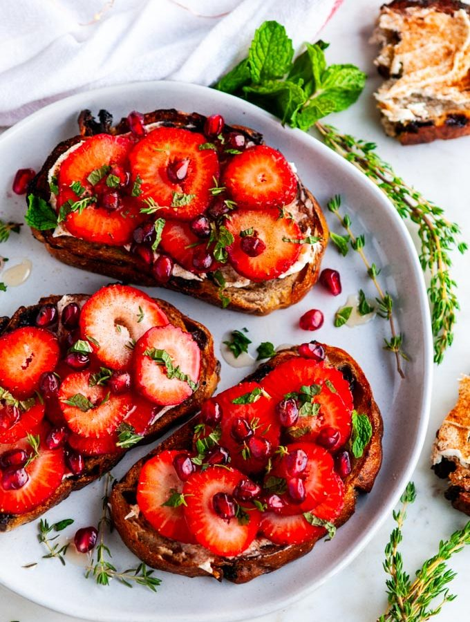 Strawberry Mascarpone Cinnamon Raisin Breakfast Toast on white plate with mint