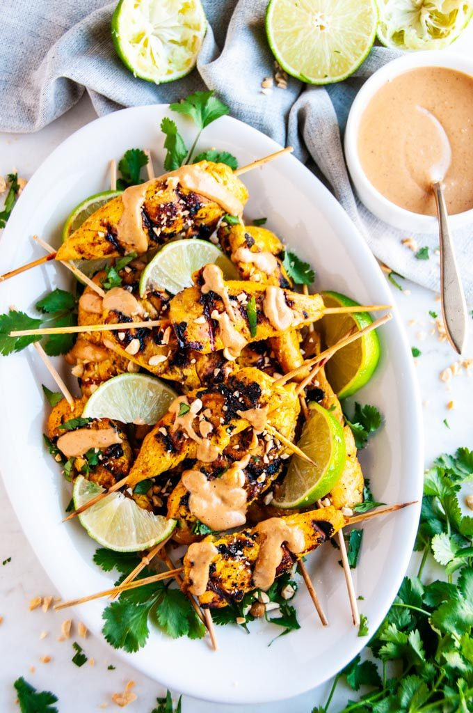 Chicken Satay Skewers with Peanut Sauce on white platter with limes and cilantro