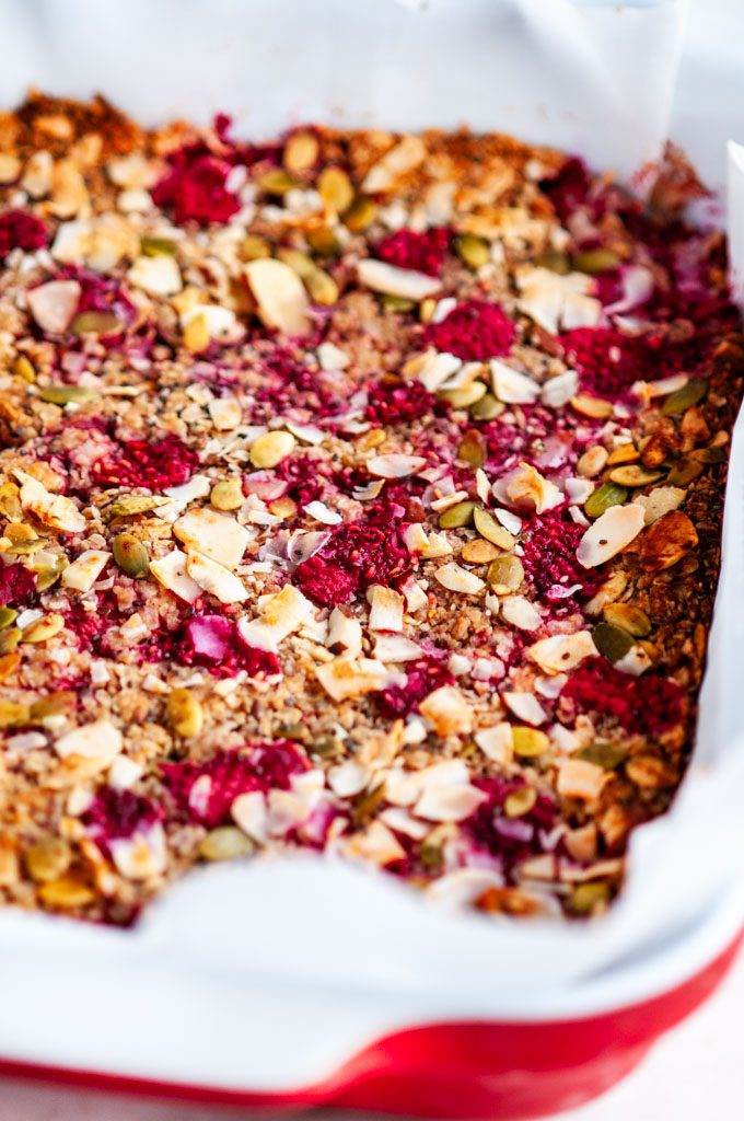 Healthy Raspberry Coconut Granola Bars sheet in red and white baking dish