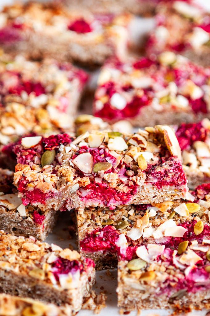 Healthy Raspberry Coconut Granola Bars on white marble with parchment paper