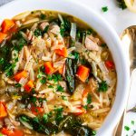 Lemon Chicken Orzo Soup white bowl with gold spoon and gray towel