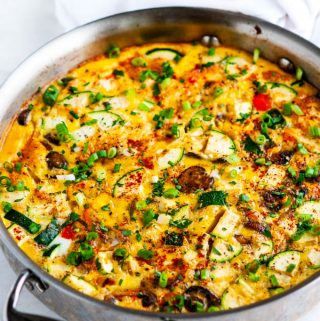 Loaded Veggie Frittata in all clad skillet on white marble
