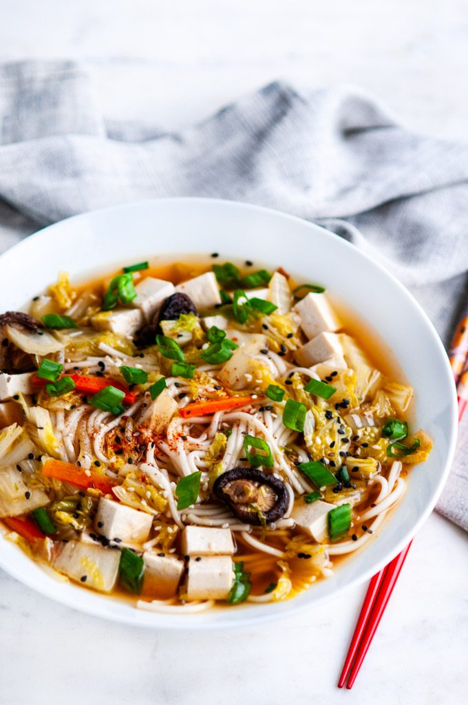 Shiitake Mushroom Udon Noodle Soup in white bowl with red chopsticks and gray towel