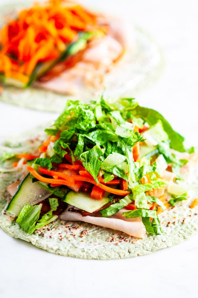 Turkey BLT wraps with shredded lettuce and carrots on white marble