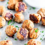 Baked Turkey Meatballs on sheet pan with parchment paper and marinara dipping sauce