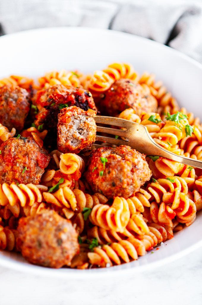 Baked Turkey Meatballs with marinara sauce pasta and gold fork in a white bowl