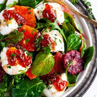 Burrata Citrus Green Salad on white plate gray platter with gold fork
